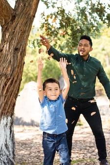 Jonge man en zijn zoon spelen en droge bladeren gooien in het bos
