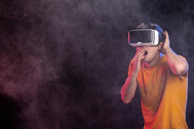 Jonge man eng spel spelen in de donkere ondergrond van de virtuele realiteit