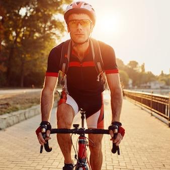 Jonge man fietsen racefiets in de avond