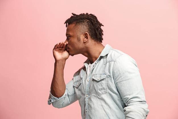 Jonge man fluisteren een geheim achter zijn hand over roze