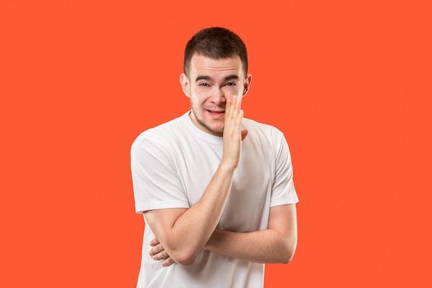 Jonge man fluistert een geheim achter zijn hand.