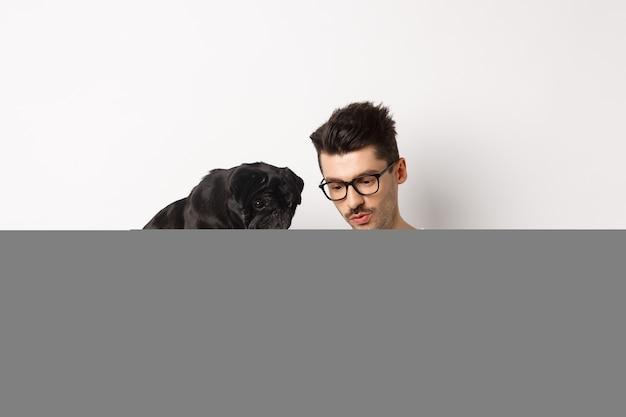Jonge man foto's op smartphone tonen aan schattige hond, huisdiereneigenaar en pug staren naar mobiele telefoon, wit