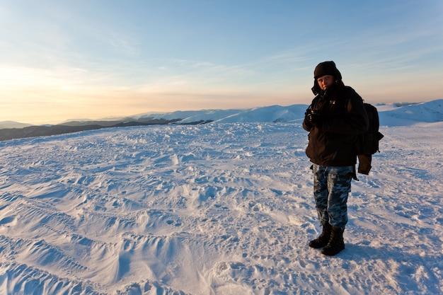 Jonge man fotograaf in winter kleding staan en foto met camera maken