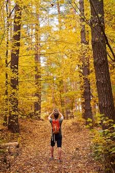Jonge man-fotograaf wandelen in het gouden herfstbos en foto's maken.