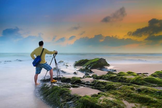 Jonge man fotograferen met statief op het strand na zonsondergang