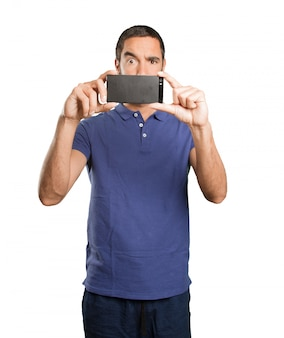 Jonge man fotograferen met zijn mobiele telefoon op een witte achtergrond