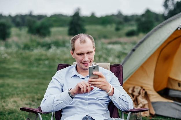 Jonge man freelancer zittend op een stoel en het gebruik van slimme telefoon. ontspannen voor tent op camping in bos of weide. werken op afstand en buitenactiviteiten in de zomer.