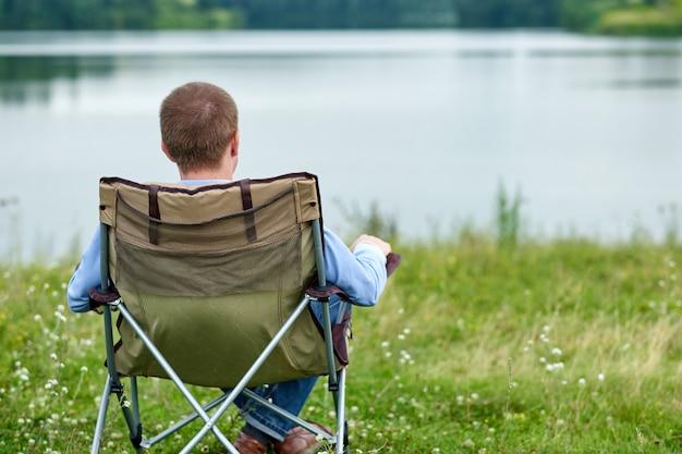 Jonge man freelancer zittend op een stoel en ontspannen in de natuur in de buurt van het meer. buitenactiviteiten in de zomer.