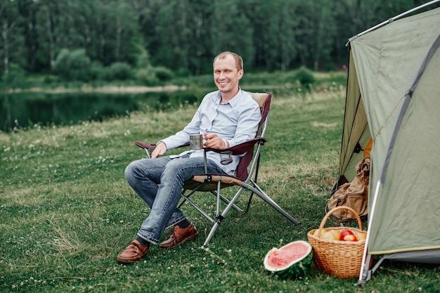 Jonge man freelancer zittend op een stoel en ontspannen voor tent op camping in bos of weide. buitenactiviteiten in de zomer.