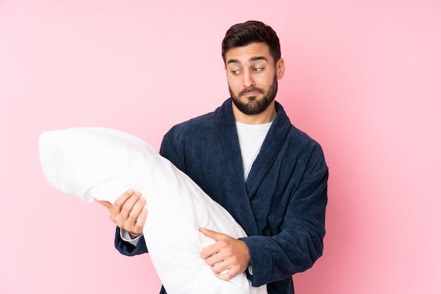 Jonge man gaan slapen op roze muur