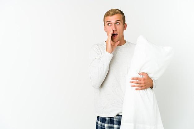 Jonge man gaat slapen geïsoleerd op een witte muur achterkant van het hoofd aanraken, denken en een keuze maken