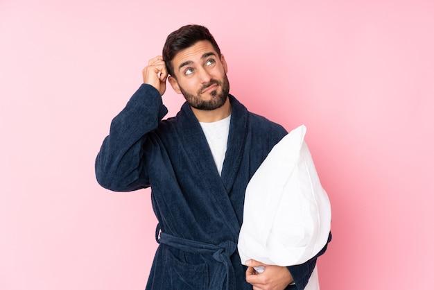 Jonge man gaat slapen geïsoleerd op roze muur twijfels hebben en met verwarde gezichtsuitdrukking
