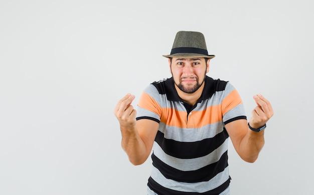Jonge man gebaren als hulp nodig hebben in t-shirt, hoed en nederig, vooraanzicht kijken.