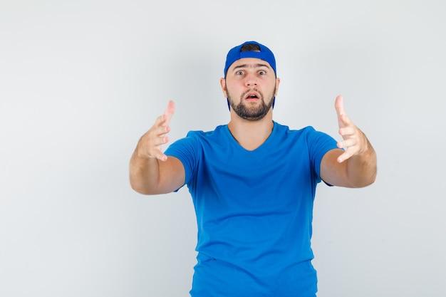 Jonge man gebaren alsof hij iets zwaars vasthoudt in blauw t-shirt en pet vooraanzicht.
