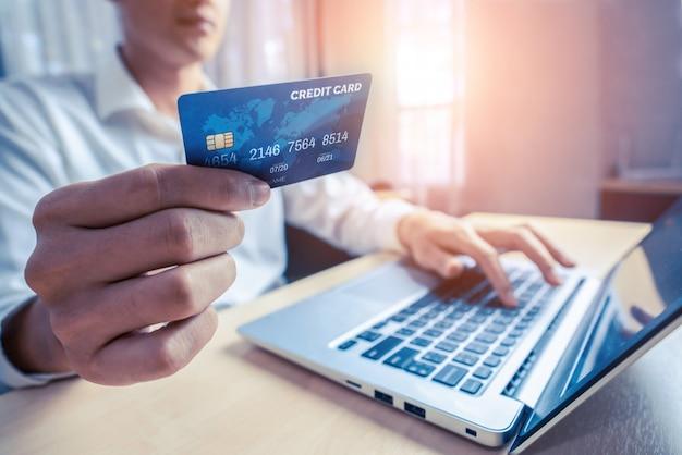 Jonge man gebruik creditcard voor online winkelen