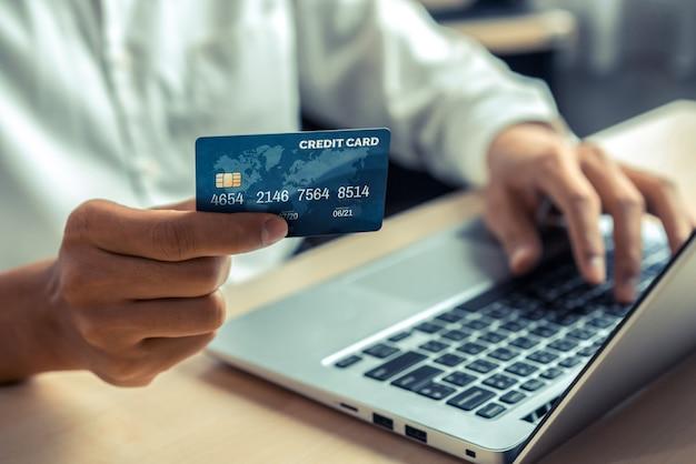 Jonge man gebruikt creditcard om online te betalen op laptop computertoepassing of website