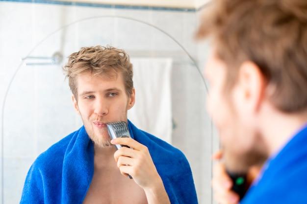 Jonge man gebruikt elektrische trimmer scheren tegenover de spiegel