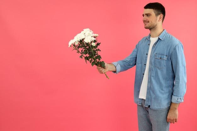 Jonge man geeft bloemen op roze achtergrond.