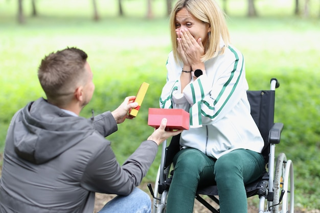 Jonge man geeft cadeau aan gelukkige vrouw in rolstoelondersteuning voor mensen met een handicap concept