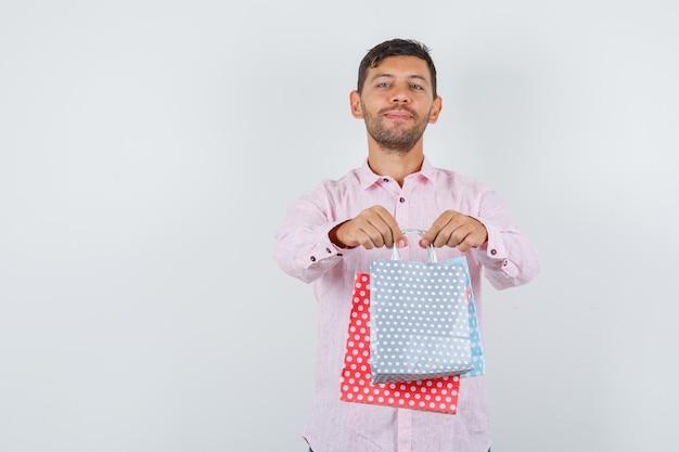 Jonge man geeft je papieren zakken in shirt en kijkt vrolijk, vooraanzicht.