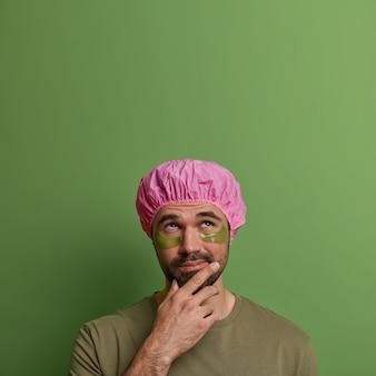 Jonge man geeft om zijn uiterlijk, vermindert rimpels, brengt pleisters onder de ogen aan na het douchen, houdt kin vast en kijkt bedachtzaam naar boven, geïsoleerd op groene muur, lege ruimte voor tekst
