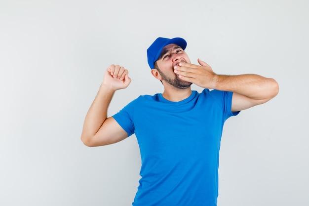 Jonge man geeuwen en zich uitstrekt in blauw t-shirt en pet en slaperig kijken