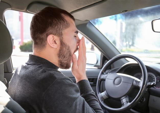 Jonge man geeuwen in auto tijdens verkeersopstopping