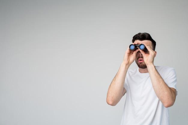 Jonge man geïsoleerd op achtergrond met verrekijkers