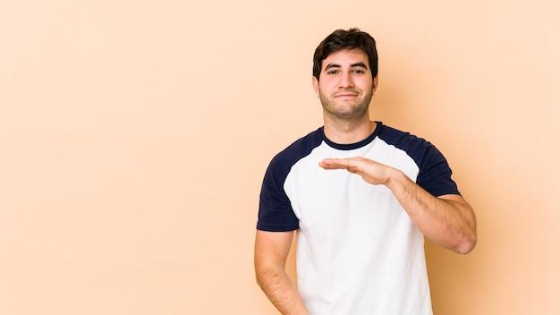 Jonge man geïsoleerd op beige met iets met beide handen, productpresentatie.