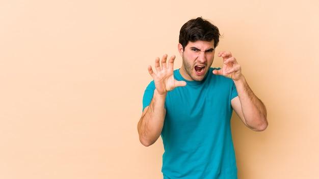 Jonge man geïsoleerd op beige met klauwen die een kat, agressief gebaar imiteren.