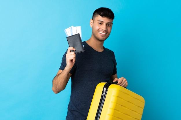 Jonge man geïsoleerd op blauw in vakantie met koffer en paspoort