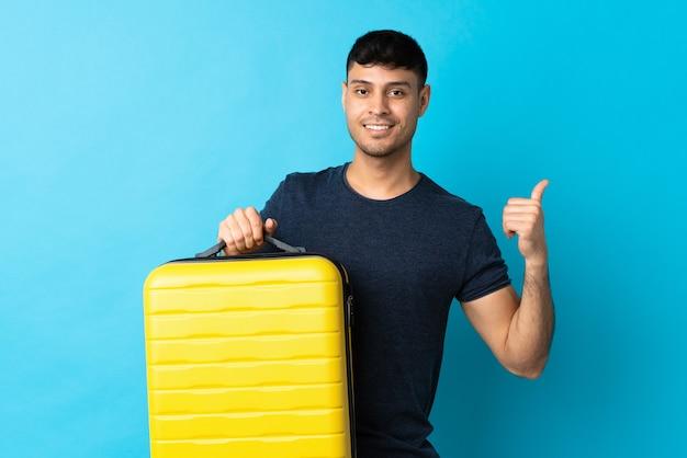 Jonge man geïsoleerd op blauw in vakantie met reiskoffer en met duim omhoog
