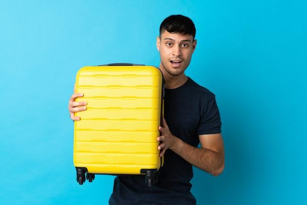 Jonge man geïsoleerd op blauw in vakantie met reiskoffer en verrast