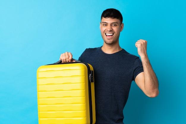 Jonge man geïsoleerd op blauw in vakantie met reiskoffer