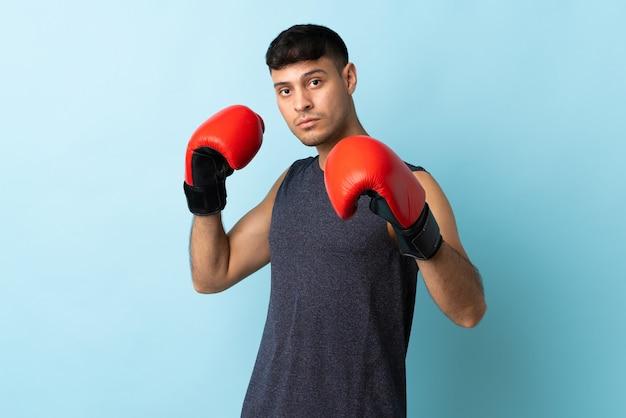Jonge man geïsoleerd op blauw met bokshandschoenen