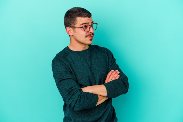 Jonge man geïsoleerd op blauwe muur dromen van het bereiken van doelen en doeleinden