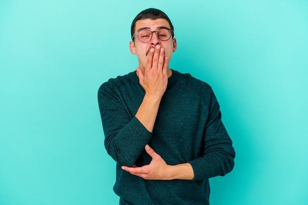 Jonge man geïsoleerd op blauwe muur geeuwen met een moe gebaar dat mond bedekt met hand