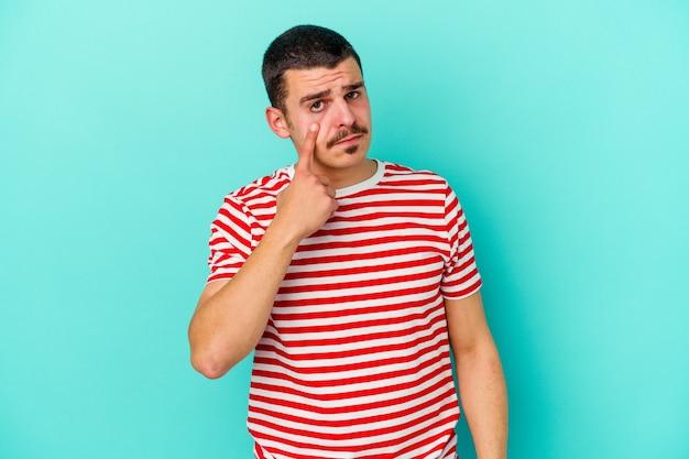 Jonge man geïsoleerd op blauwe muur huilen, ongelukkig met iets, pijn en verwarring concept