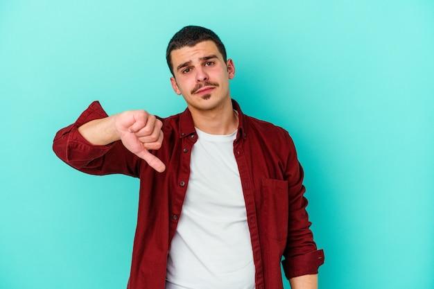 Jonge man geïsoleerd op blauwe muur met een afkeer gebaar, duimen naar beneden. meningsverschil concept