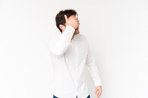 Jonge man geïsoleerd op een witte achtergrond heeft betrekking op ogen met handen, glimlacht in het algemeen wachtend op een verrassing.