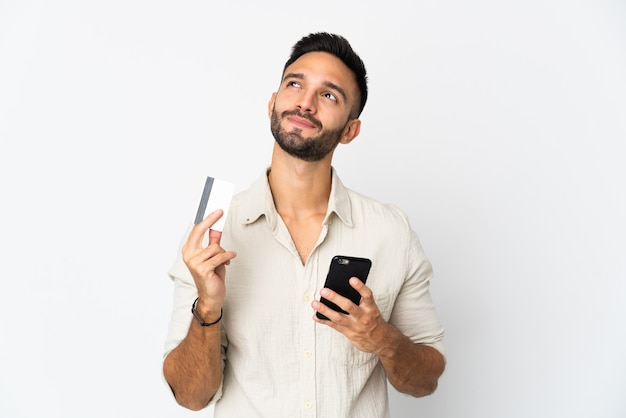 Jonge man geïsoleerd op een witte muur te kopen met de mobiele telefoon met een creditcard tijdens het denken
