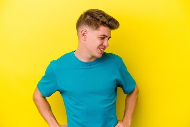 Jonge man geïsoleerd op gele muur zelfverzekerd handen op de heupen te houden