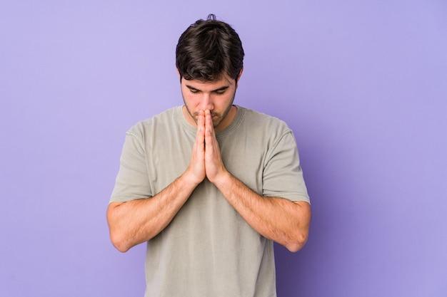 Jonge man geïsoleerd op paarse achtergrond bidden, toewijding, religieuze persoon op zoek naar goddelijke inspiratie.