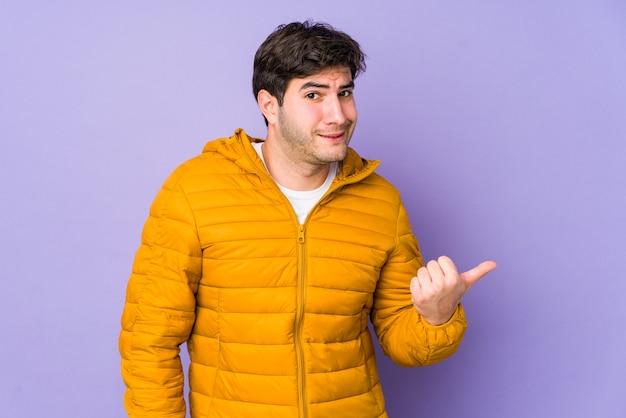 Jonge man geïsoleerd op paarse achtergrond geschokt wijzend met wijsvingers naar een kopie ruimte.