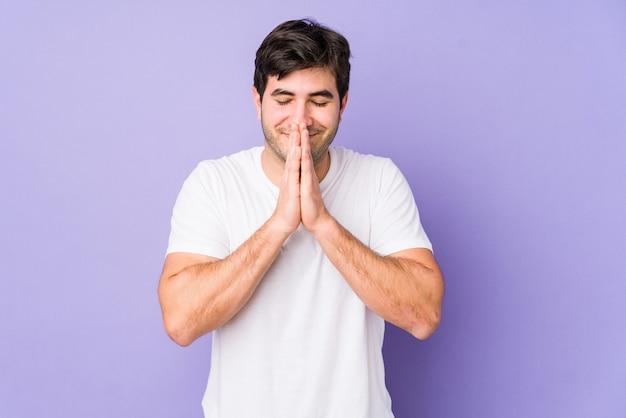 Jonge man geïsoleerd op paarse achtergrond hand in hand bidden in de buurt van de mond, voelt zich zelfverzekerd.
