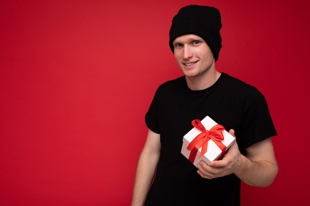 Jonge man geïsoleerd op rode achtergrond muur met zwarte hoed en zwart t-shirt met witte geschenkdoos met rood lint en camera kijken. kopieer ruimte, mockup