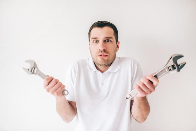 Jonge man geïsoleerd over witte muur. de verwarde kerel houdt twee sleutels in handen. reparatie man of loodgieter.