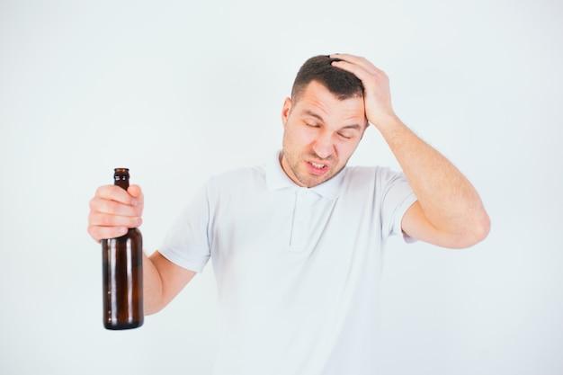 Jonge man geïsoleerd over witte muur. guy lijdt aan hoofdpijn en kater. houd de fles in de hand. lijd aan pijn.