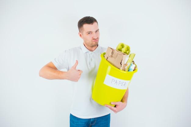 Jonge man geïsoleerd over witte muur. man houdt gele emmer met papier erin. materiaal inzamelen voor recycling. geen verspilde levensstijl.