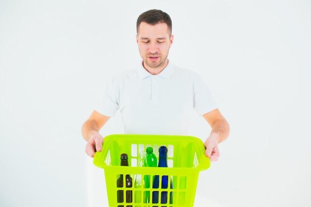 Jonge man geïsoleerd over witte muur. man houdt groene plastic mand met flessen erin. recycling en verantwoord gebruik. geen verspilde levensstijl.